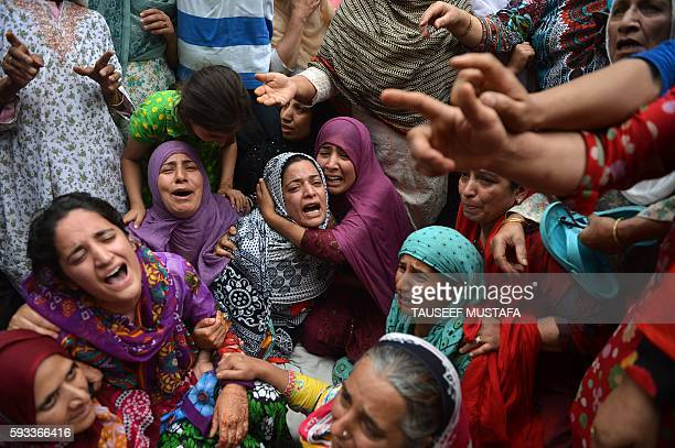 TOPSHOT Relatives of Kashmiri teenager Irfan Ahmed who was killed by a teargas shell break down as local residents visit the family to offer their...