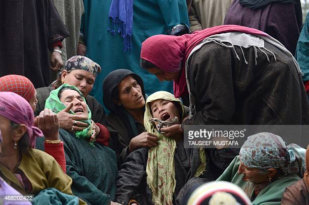 Relatives of landslide victims mourn during a funeral in the village of Laden at Chadoora some 40kms west of Srinagar on March 31 2015 Emergency...