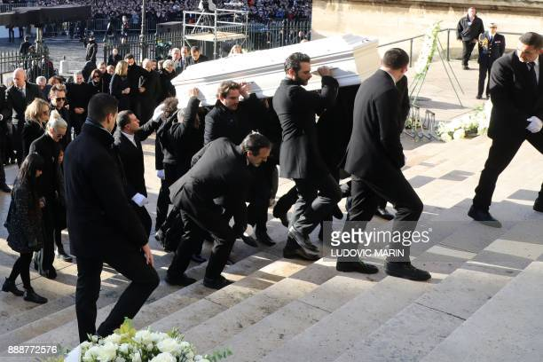 Relatives of late French singer Johnny Hallyday carry his coffin French singer Maxim Nucci aka Yodelice and his manager Sebastien Farran as they...