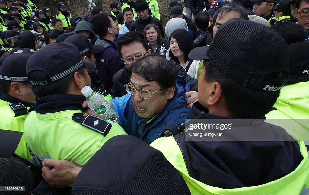 Relatives of missing passengers from the sunken ferry scuffle with police as they try to go to the presidential house on April 20, 2014 in Jindo-gun, South Korea. At least forty six people are reported dead, with 256 still missing. The ferry identified as the Sewol was carrying about 470 passengers, including the students and teachers, traveling to Jeju Island.