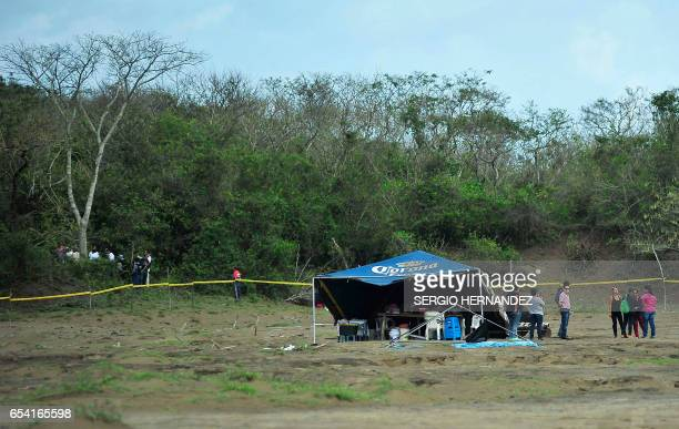 Relatives of missing people and forensic experts gather next to mass graves on the outskirts of Veracruz Veracruz State Mexico on March 16 2017 At...