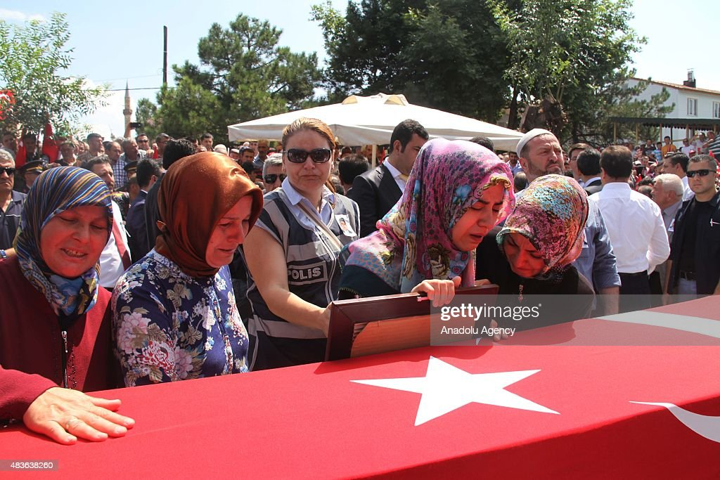 Relatives of Mustafa Yahya Mertcan mourn over his coffin during his funeral ceremony in Cankiri Turkey on August 11 2015 Four policemen were killed...