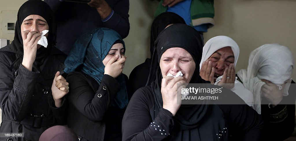 Relatives of Naji Balbisi, a 19-year-old Palestinian shot by Israeli troops, mourn during his funeral in the West Bank town of Anabta near Tulkarem on April 4, 2013. The West Bank simmered with anger as thousands joined the funeral of prisoner Maisara Abu Hamdiyeh who died in an Israeli jail and similar numbers gathered to bury two teens shot dead overnight during clashes over the death of the prisoner, Israeli and Palestinian sources said.