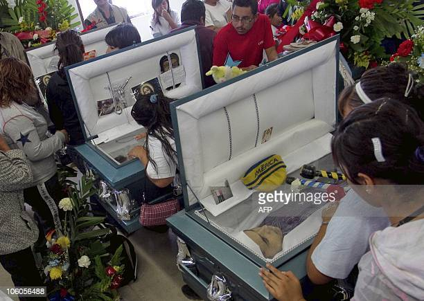 Relatives of one of the 14 partygoers killed when gunmen broke into a home in Ciudad Juarez on October 23 carry a coffin during the funeral in this...