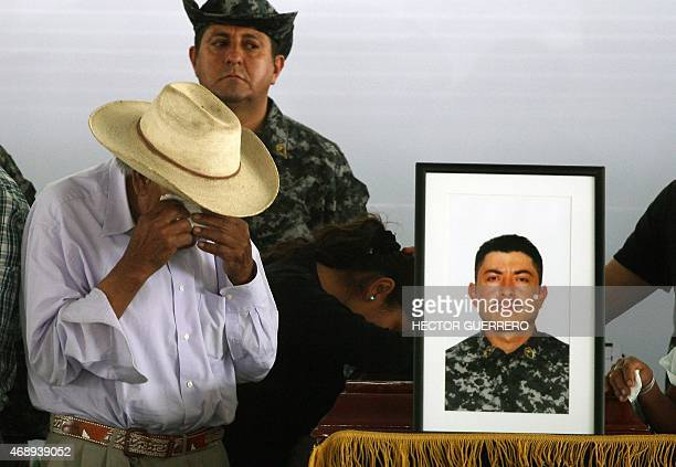 Relatives of one of the 15 police members killed during an ambush by criminal gang assassins on April 6 mourn next to his coffin during the funeral...