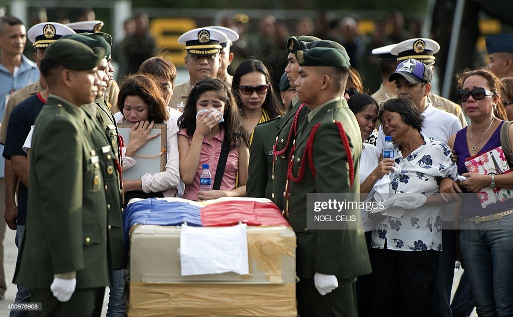 Relatives of one of the five dead soldiers that arrived the Villamor Airbase in Manila cry in front of the flag draped coffin on June 21, 2014. Ten Muslim extremists and seven soldiers were killed in one of the bloodiest clashes in the southern Philippines in recent months, the military said.