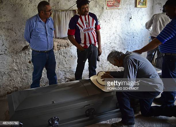 Relatives of one victims of the truck accident cry next to its coffins in Santa Rosa town in Zacatecas State on July 30 2015 A truck plowed into a...