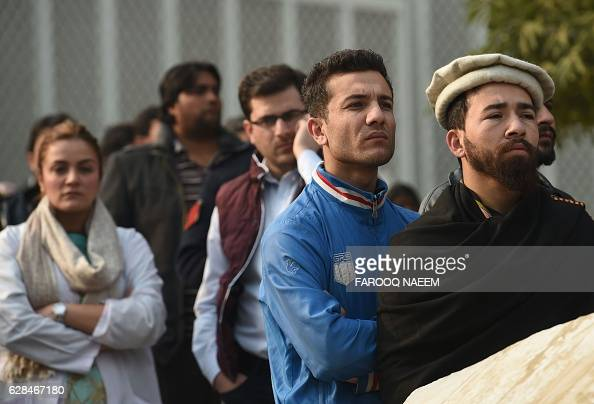 Relatives of Pakistani plane crash victims look on as ambulances carrying coffins arrive at the Pakistan Institute of Medical Sciences hospital in...