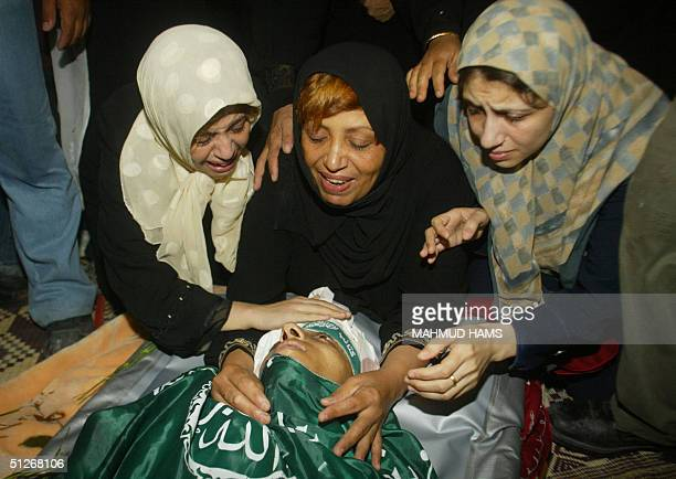 Relatives of Palestinian militant Aref Gendia mourn over his body during the funeral of fourteen Hamas activists in Gaza City 07 September 2004...