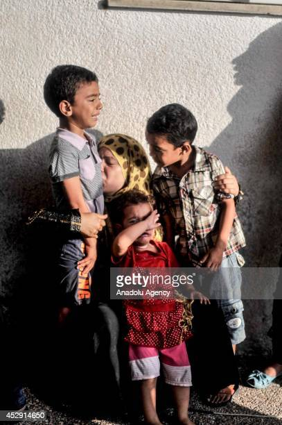 Relatives of Palestinians killed in an Israeli strike on a UN school mourn outside the Kamal Adwan hospital in Beit Lahia Gaza on July 30 2014 The...