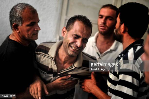 Relatives of Palestinians killed in an Israeli strike on a UN school cries at Kamal Adwan hospital in Beit Lahia Gaza on July 30 2014 The death toll...