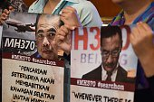 Relatives of passengers missing on Malaysia Airlines MH370 holds placards during a press conference after meeting with the Joint Agency Coordination...