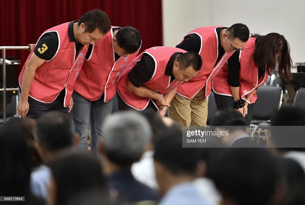 Relatives of people injured in the water park explosion last year bow to thank the public during a music concert to mark the first anniversary of the accident in Taipei on June 26, 2016. Taiwan commemorated a water park explosion that left 15 dead and hundreds injured with a memorial concert on the eve of its one-year anniversary as victims and their relatives demanded justice after only a party organiser was sentenced over the incident. The accident happened in June 2015 at the Formosa Fun Coast water park near Taipei, when clouds of multi-coloured corn starch sprayed on revellers at a 'colour party' ignited after heat from stage lights triggered a blast that ripped through the crowd. / AFP / SAM YEH