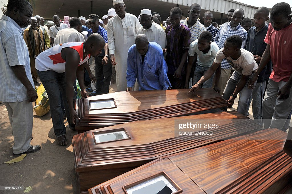 Relatives of people killed in a stampede carry a coffin of a victim, in front of the Treichville morgue in Abidjan, on January 9, 2013. The official death toll rose to 63 two days after a New Year stampede, which broke out among crowds returning from a fireworks display in the economic capital Abidjan.