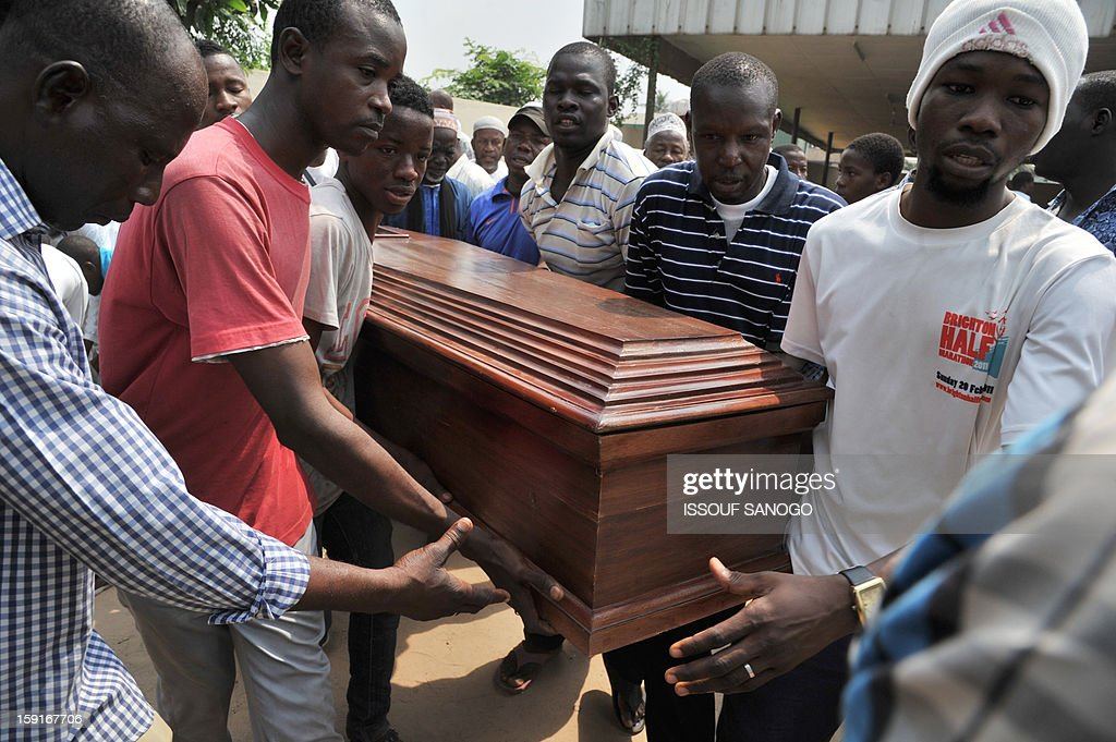 Relatives of people killed in a stampede carry the coffin of a victim, at the Treichville morgue in Abidjan, on January 9, 2013. The official death toll rose to 63 two days after a New Year stampede, which broke out among crowds returning from a fireworks display in the economic capital Abidjan.