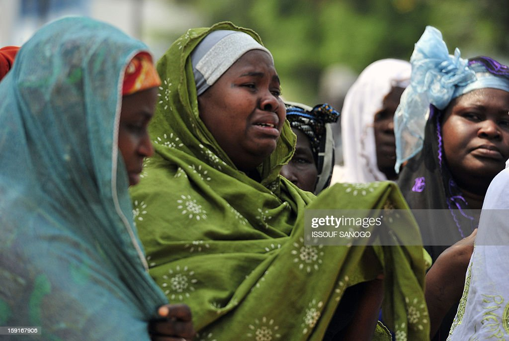 Relatives of people killed in a stampede cry during a funeral ceremony at the Treichville morgue in Abidjan, on January 9, 2013. The official death toll rose to 63 two days after a New Year stampede, which broke out among crowds returning from a fireworks display in the economic capital Abidjan.