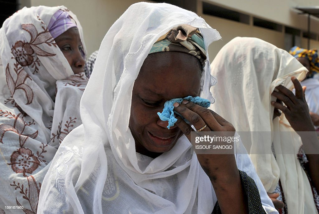 Relatives of people killed in a stampede cry during a funeral ceremony at the Treichville morgue in Abidjan, on January 9, 2013. The official death toll rose to 63 two days after a New Year stampede, which broke out among crowds returning from a fireworks display in the economic capital Abidjan. AFP PHOTO / ISSOUF SANOGO
