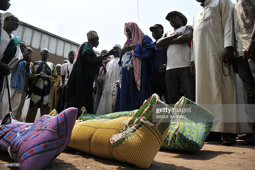 Relatives of people killed in a stampede gather to pray in front of bodies of victims, at the Treichville morgue in Abidjan, on January 9, 2013. The official death toll rose to 63 two days after a New Year stampede, which broke out among crowds returning from a fireworks display in the economic capital Abidjan.