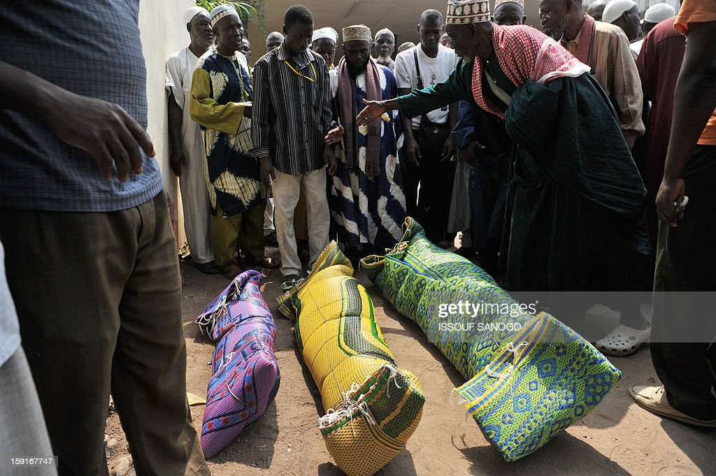Relatives of people killed in a stampede gather to pray in front of bodies of victims, at the Treichville morgue in Abidjan, on January 9, 2013. The official death toll rose to 63 two days after a New Year stampede, which broke out among crowds returning from a fireworks display in the economic capital Abidjan. AFP PHOTO / ISSOUF SANOGO
