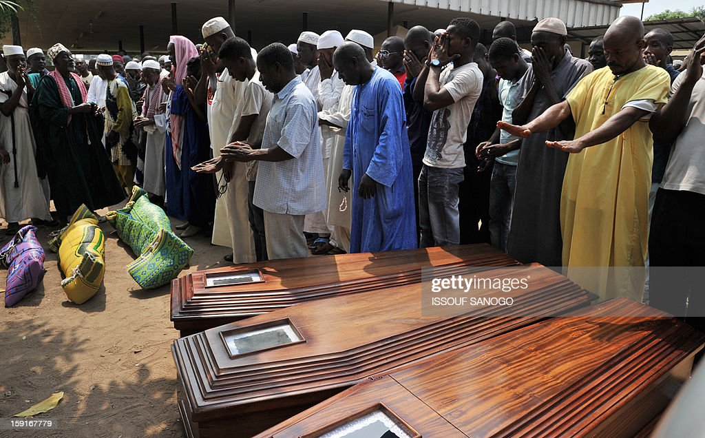 Relatives of people killed in a stampede pray in front of bodies of victims, at the Treichville morgue in Abidjan, on January 9, 2013. The official death toll rose to 63 two days after a New Year stampede, which broke out among crowds returning from a fireworks display in the economic capital Abidjan.