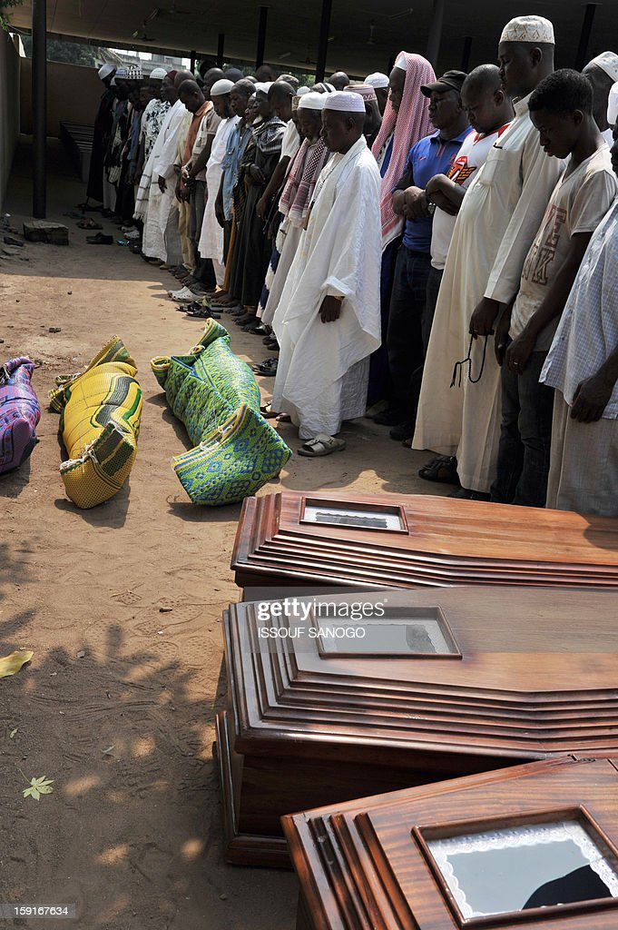 Relatives of people killed in a stampede pray next to coffins and bodies of victims, in front of the Treichville morgue in Abidjan, on January 9, 2013. The official death toll rose to 63 two days after a New Year stampede, which broke out among crowds returning from a fireworks display in the economic capital Abidjan.