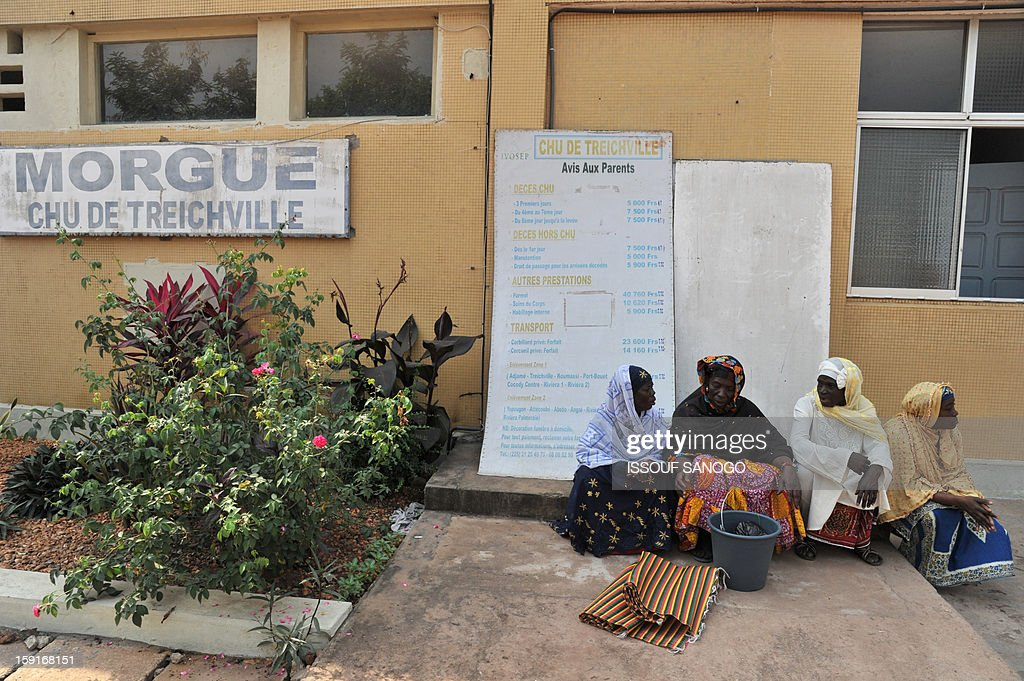 Relatives of people killed in a stampede sit in front of the Treichville morgue as they wait to retrieve the bodies of the victims in Abidjan, on January 9, 2013. The official death toll rose to 63 two days after a New Year stampede, which broke out among crowds returning from a fireworks display in the economic capital Abidjan.