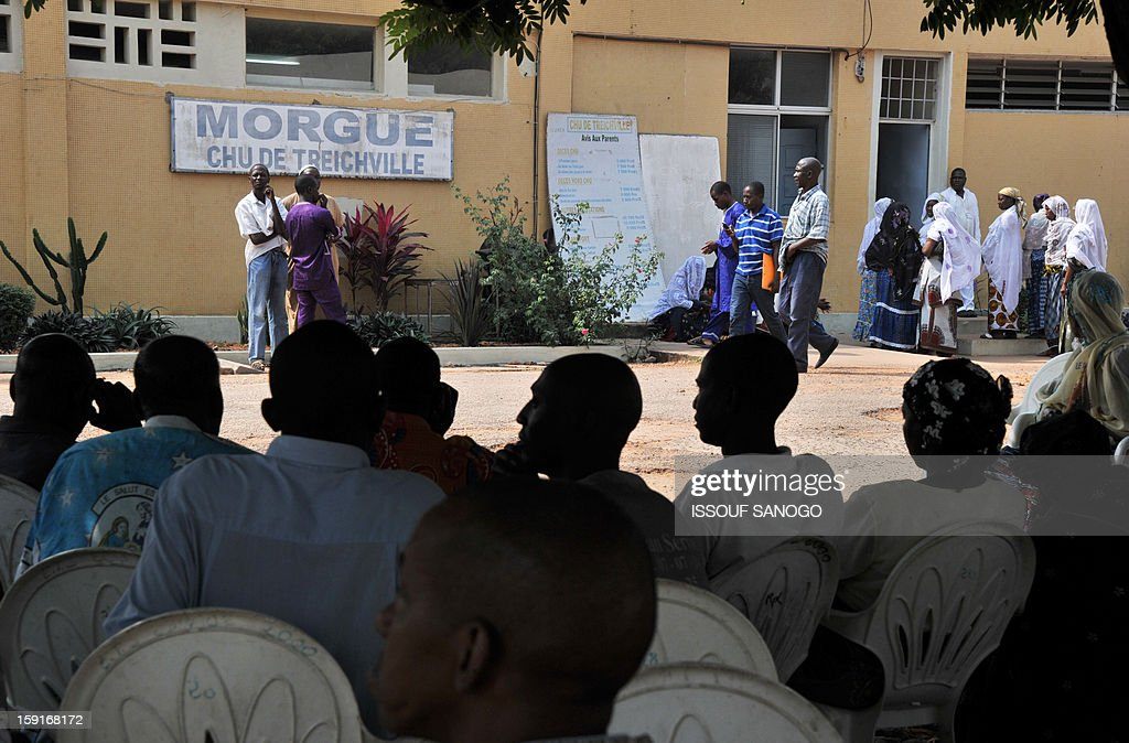 Relatives of people killed in a stampede wait in front of the Treichville morgue to retrieve the bodies of the victims in Abidjan, on January 9, 2013. The official death toll rose to 63 two days after a New Year stampede, which broke out among crowds returning from a fireworks display in the economic capital Abidjan. AFP PHOTO / ISSOUF SANOGO
