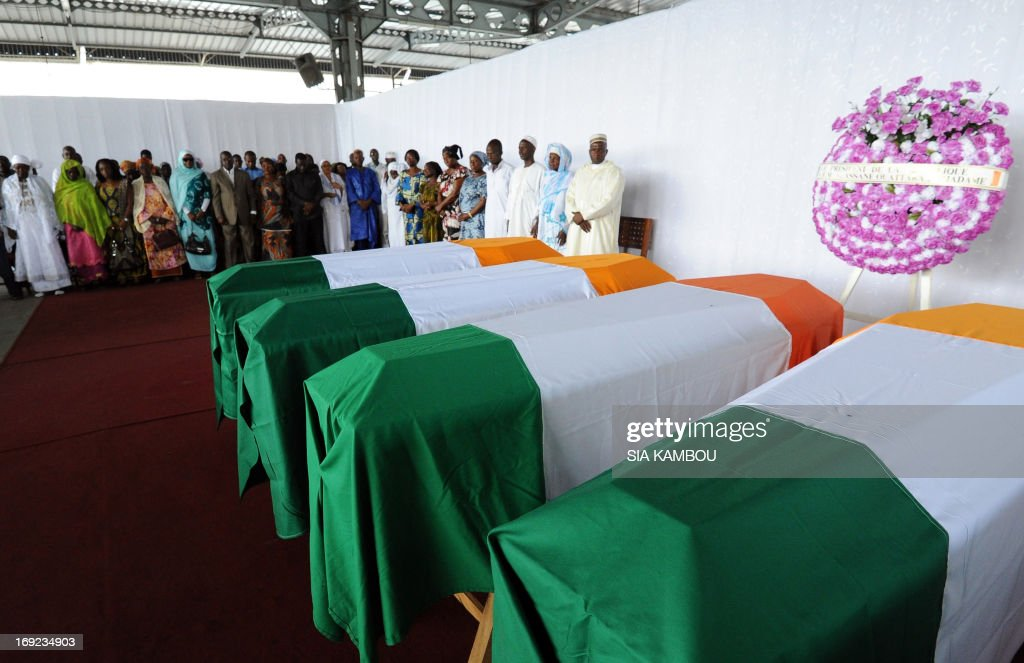 Relatives of people who lost their lives during the post electoral violence stand in front of coffins bearing bodies and remains of the victims and covered with the Ivorian national flag, during a ceremony hosted by Ivorian Justice and Human Rights minister, on May 22, 2013 in Abidjan. Ivory Coast is still recovering from a political and military crisis between December 2010 and April 2011 sparked by Laurent Gbagbo's refusal to step down after his arch-rival Alassane Ouattara was declared the winner of presidential elections.The conflict left 3,000 people dead before Gbagbo was arrested and Ouattara assumed power.