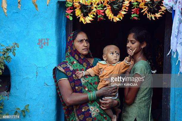 Relatives of Phool Bai Srivastava who died after undergoing a mass sterilisation operation in a governmentrun programme take care of her surviving...