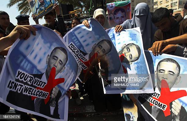 Relatives of prisoners of Palestinians held in Israeli jails burn pictures of US President Barack Obama during a protest against his visit to the...