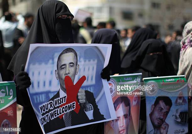 Relatives of prisoners of Palestinians held in Israeli jails hold up crossed portraits of US President Barack Obama during a protest against his...