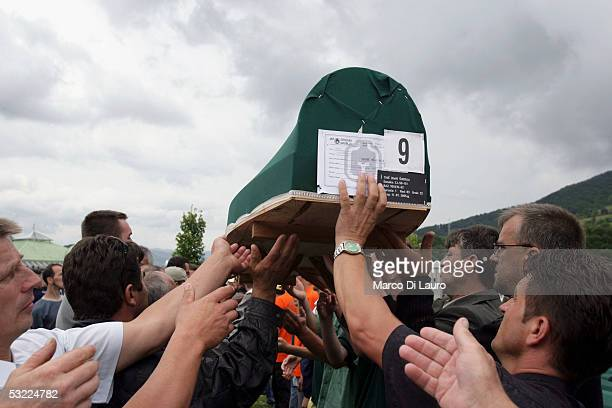 SREBRENICA BOSNIA HERZEGOVINA JULY 11 Relatives of some of the Srebrenica massacre victims form a human chain to carry one of the 610 coffins during...