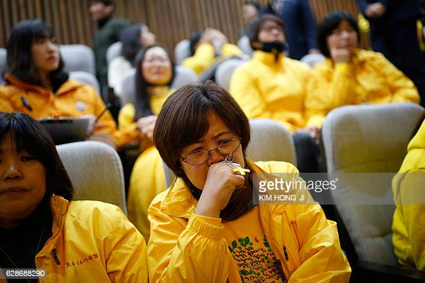 TOPSHOT Relatives of sunken ferry Sewol react as assembly Speaker Chung Syekyun announces the result of the impeachment vote on South Korean...