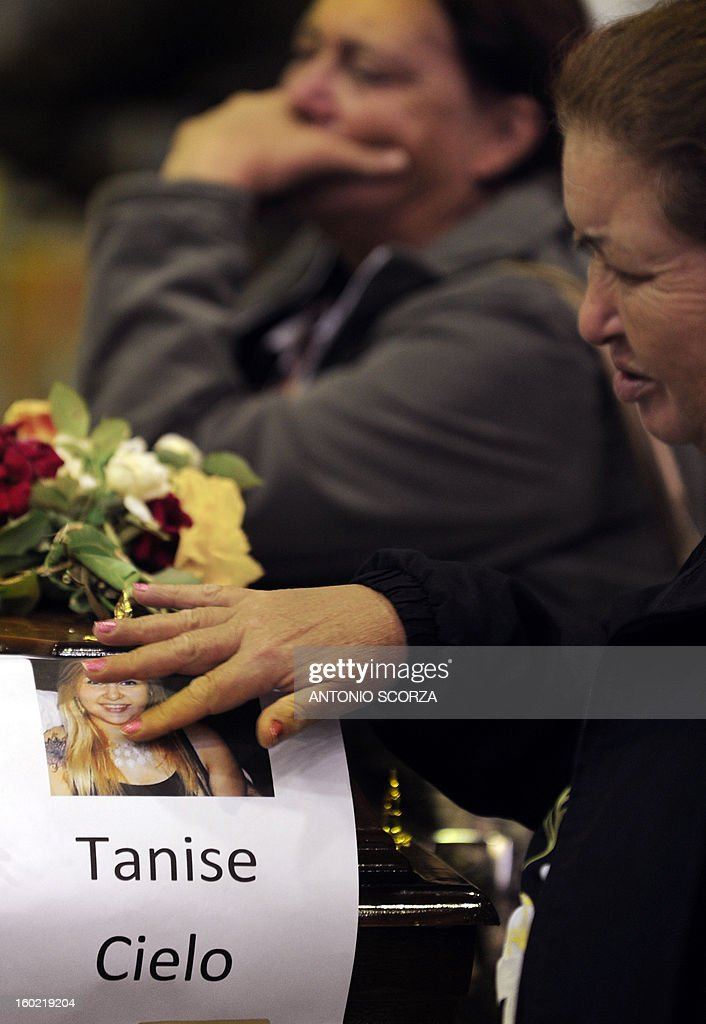 Relatives of Tanise Cielo, one of the victims killed in the Kiss night club fire, pray and mourn over her coffin at the municipal gymnasium on January 27, 2013 in Santa Maria. Brazilians were mourning the victims of a nightclub blaze in a small college town that left more than 230 people dead and over 100 injured, with many still fighting for their lives.