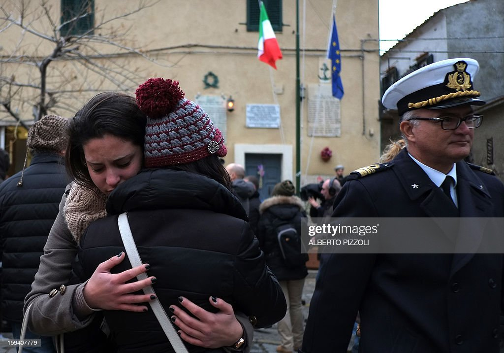 Relatives of the victims cry during the unveiling ceremony of a plaque with the names of the victims of the Costa Corncordia cruise ship in the port in the Italian island of Giglio on January 13, 2013. Survivors, grieving relatives and locals on the island of Giglio gathered on January 13 to mark the first anniversary of the Costa Concordia cruise ship disaster, which claimed 32 victims.