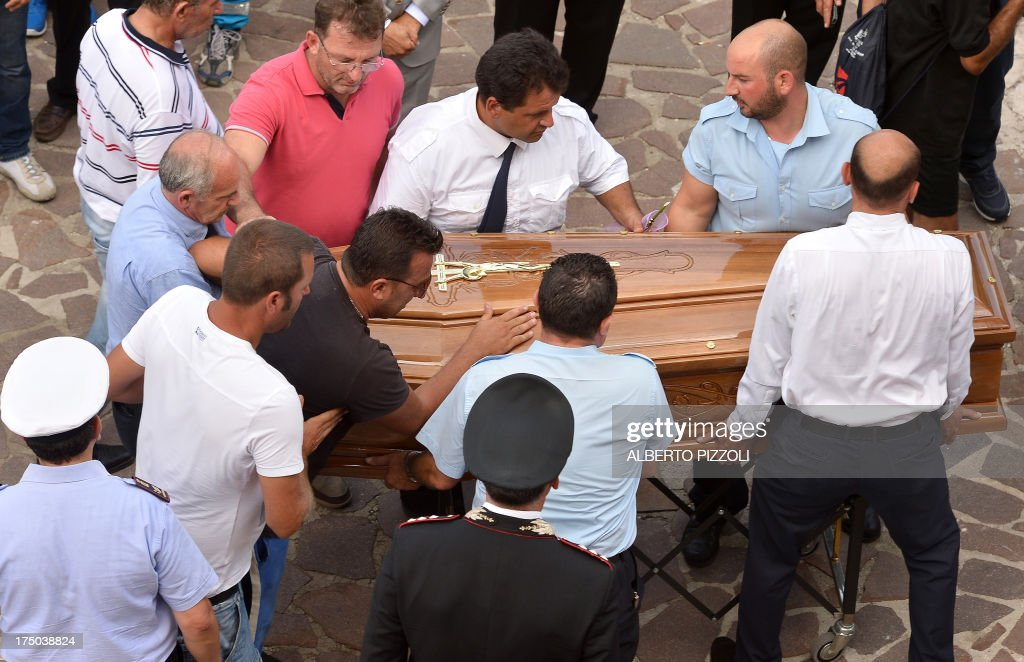 Relatives of the victims of a bus crash on the road between Monteforte Irpino and Baiano mourn on a coffin on July 29, 2013, near the morgue in Monteforte Irpino, southern Italy. A coach carrying pilgrims plunged off a motorway flyover near Naples in southern Italy, killing at least 39 people in one of the worst such accidents in Europe in recent years.