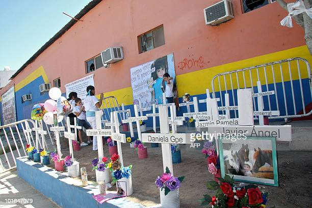Relatives of the victims of a fire at a day care center visit an altar placed in front of the burnt center in Hermosillo Sonora State Mexico on June...