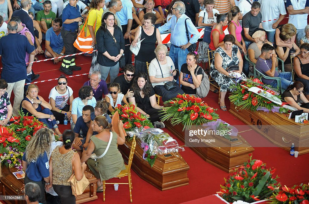 Relatives of the victims of the Monteforte Irpino coach crash are seen near their coffins during the funeral held at a local indoor sports arena on July 30, 2013 in Pozzuoli, Italy. In the second major European transport disaster in a week, 38 people were killed when a coach bus fell from a viaduct near Monteforte Irpino, Italy on July 28.