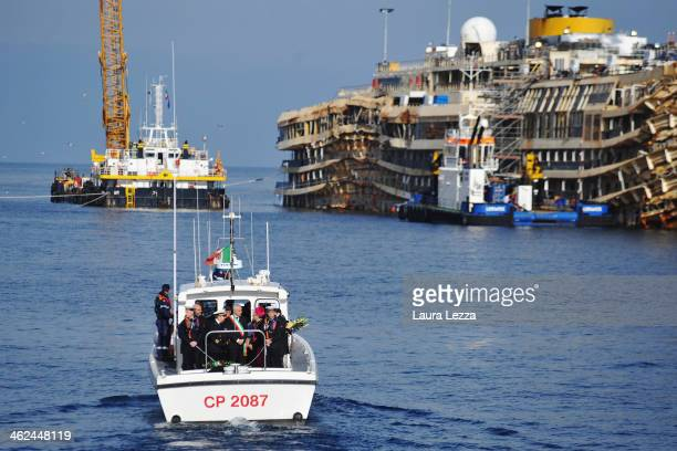 Relatives of the victims of the sunken Costa Concordia and authorities lay wreaths of flowers in front of the ship on January 13 2014 in Giglio Porto...