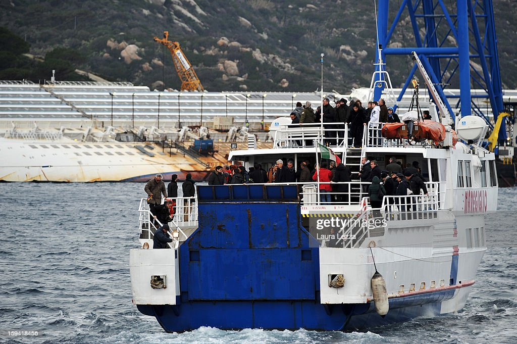 Relatives of the victims of the sunken Costa Concordia gather on a boat near the wreckage during a minute of silence to mark the exact time the ship crashed, on January 13, 2013 in Giglio Porto, Italy. A year after the sinking of the ship Costa Concordia, relatives of the victims, survivors, island residents, law enforcement and institutions gathered to mark the first anniversary and commemorate the dead. More than four thousand people were on board when the ship hit a rock off the Tuscan coast, killing 32 and leaving two people missing.