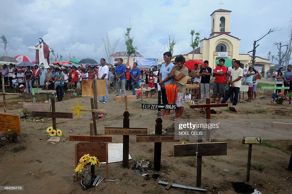 Relatives of the victims of Tyhpoon Haiyan attend an afternoon mass called 'Days of Prayer and Remembrance' held at a mass grave in front of the San Joaquin Church in Palo, Leyte on December 8, 201...