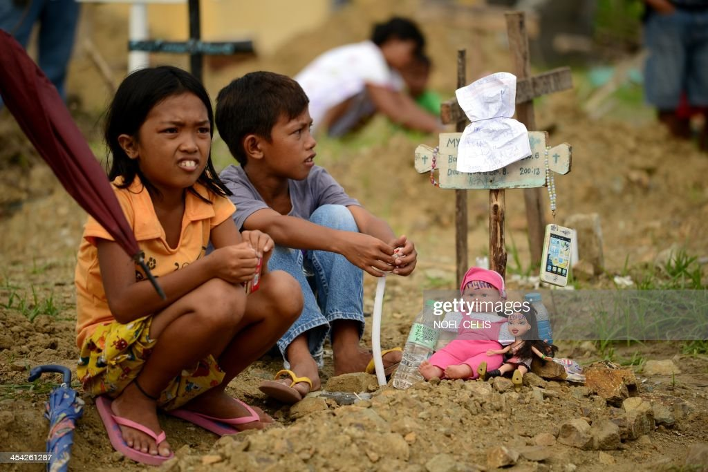 Relatives of the victims of Tyhpoon Haiyan attend an afternoon mass called 'Days of Prayer and Remembrance' held at a mass grave in front of the San Joaquin Church in Palo, Leyte on December 8, 2013, commemorating one month after the typhoon. A month after one of the strongest typhoons ever recorded hit the Philippines, masses of survivors are living amid rubble in rebuilt shanty homes and experts warn rebuilding destroyed communities will take years. AFP PHOTO / Noel Celis