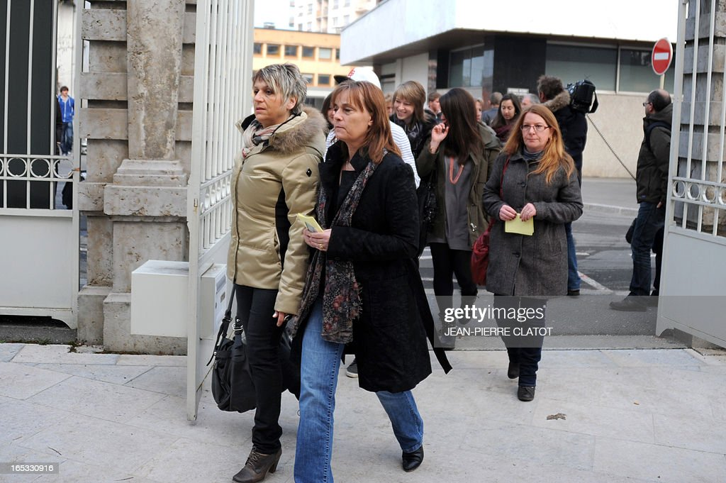 Relatives of the victims, who were killed when their school bus was hit on June 2, 2008 by a train on a railway crossing in the eastern French town of Allinges, arrive on April 3, 2013 at the courthouse for the opening of the trial in the Alpine city of Thonon-les-Bains. School bus driver Jean-Jacques Prost, the state-owned railway company SNCF and rail operator Reseau Ferre de France are charged with involuntary homicides after a train hit the school bus carrying teenagers, killing seven students and wounding 25. One of the teachers, who survived the crash, later committed suicide. AFP PHOTO / JEAN-PIERRE CLATOT