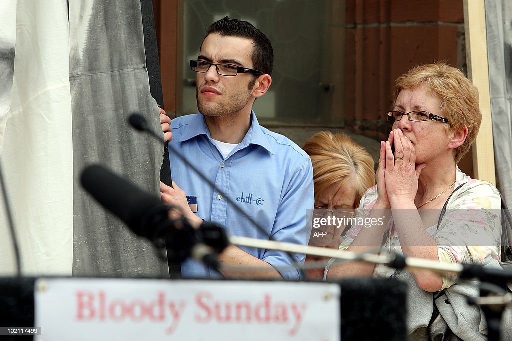 Relatives of those killed on Bloody Sunday listen to a statement by British Prime Minister David Cameron after reading a copy of the long-awaited Saville Inquiry report into Bloody Sunday, outside the Guildhall in Londonderry on June 15, 2010. Publication of the report was greeted with cheers in Londonderry, Northern Ireland's second city, where relatives of those who died joined thousands waiting to see the contents of the 5,000-page report. The killings, when British soldiers opened fire on a civil rights march in Londonderry, was one of the most controversial in Northern Ireland's history, and there had been fears the report could re-open wounds. AFP PHOTO / POOL / Paul Faith