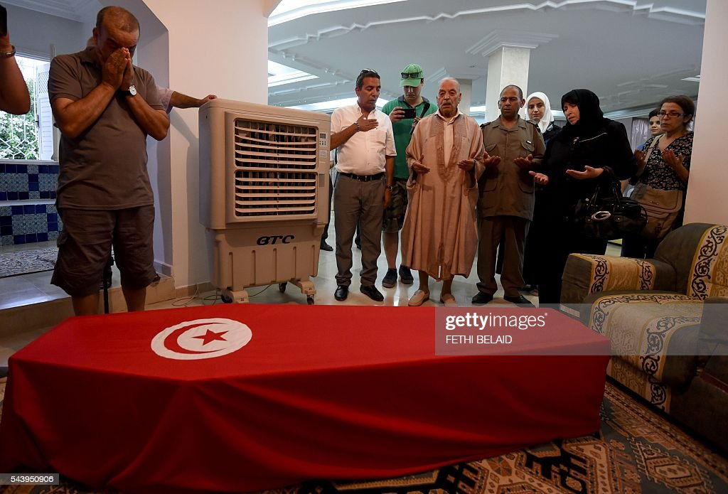 Relatives of Tunisian doctor Fathi Bayoudh, who was killed in the Istanbul airport attack blamed on the Islamic State (IS) group on June 28, pray over his coffin during a mourning ceremony at his house in Tunis on June 30, 2016, ahead of his funeral. Bayoudh, who was killed in the Istanbul airport attack, was in Turkey to secure the release of his son detained for joining the jihadists, diplomats said on June 30, 2016. / AFP / FETHI
