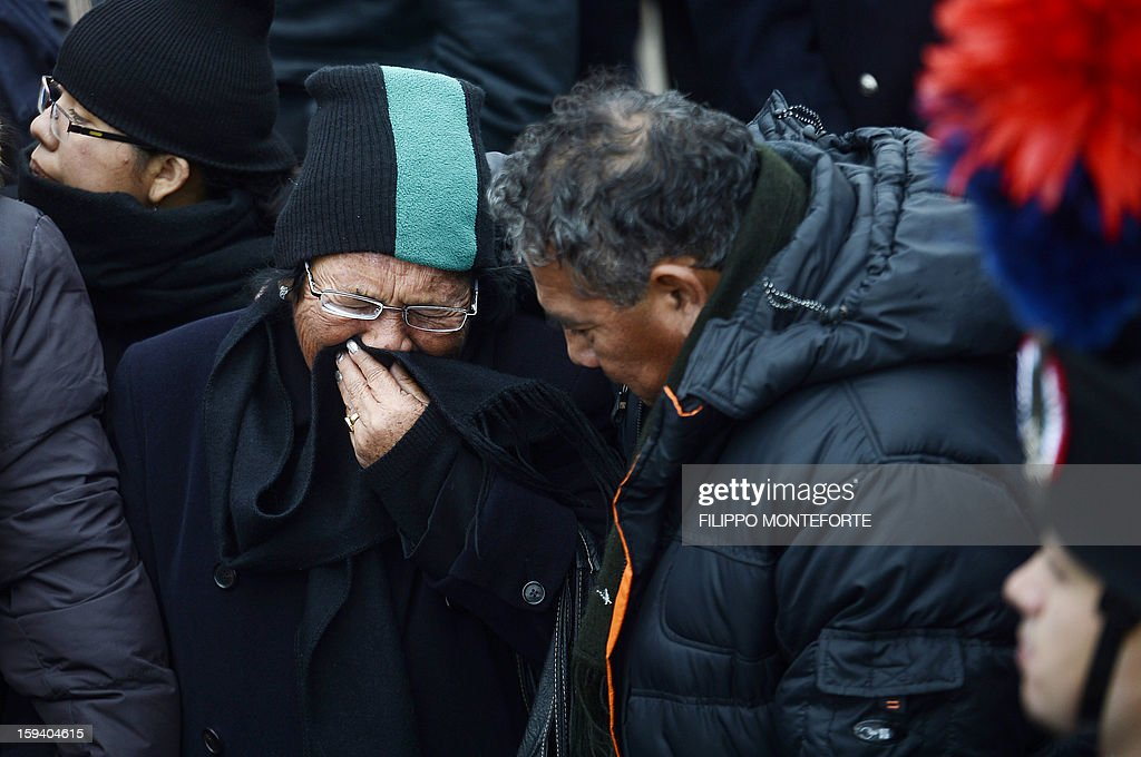 Relatives of victimes cry in front of the commemorative board after it was unveiled in the port of the Italian island of Giglio on January 13, 2013. Survivors, grieving relatives and locals on the island of Giglio gathered Sunday to mark the first anniversary of the Costa Concordia cruise ship disaster, which claimed 32 victims.