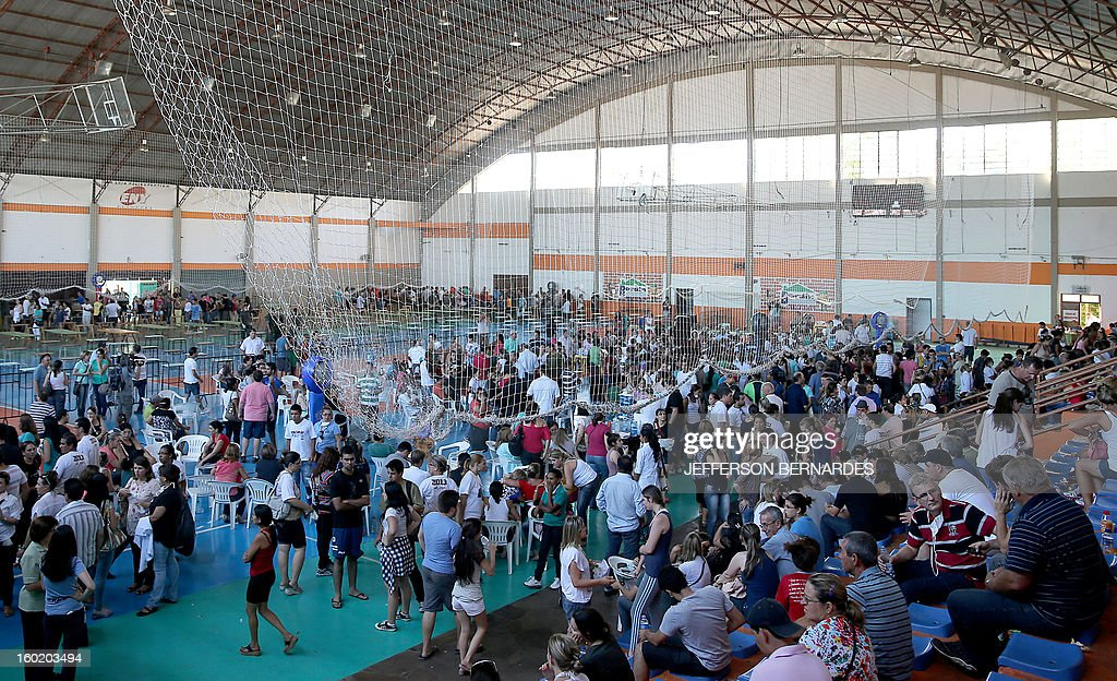 Relatives of victims from a fire that broke out at a nightclub attend their funeral in Santa Maria, 550 Km from Porto Alegre, southern Brazil on January 27, 2013. At least 232 people died and 131 were injured early Sunday when a fire tore through a nightclub packed with university students in the southern Brazilian city of Santa Maria, police said. AFP PHOTO / Jefferson BERNARDES