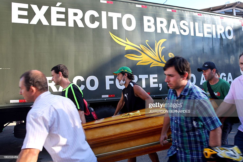 Relatives of victims from a fire that broke out at a nightclub carry a coffin during their funeral in Santa Maria, 550 Km from Porto Alegre, southern Brazil on January 27, 2013. At least 232 people died and 131 were injured early Sunday when a fire tore through a nightclub packed with university students in the southern Brazilian city of Santa Maria, police said. AFP PHOTO / Jefferson BERNARDES