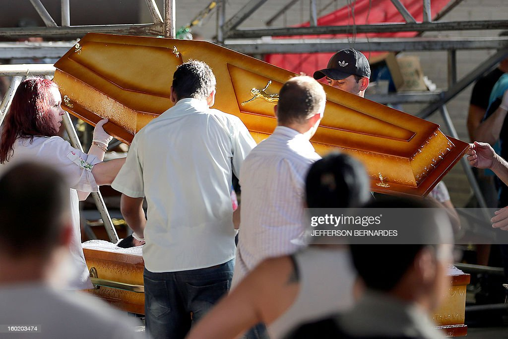 Relatives of victims from a fire that broke out at a nightclub close a coffin during their funeral in Santa Maria, 550 Km from Porto Alegre, southern Brazil on January 27, 2013. At least 232 people died and 131 were injured early Sunday when a fire tore through a nightclub packed with university students in the southern Brazilian city of Santa Maria, police said. AFP PHOTO / Jefferson BERNARDES