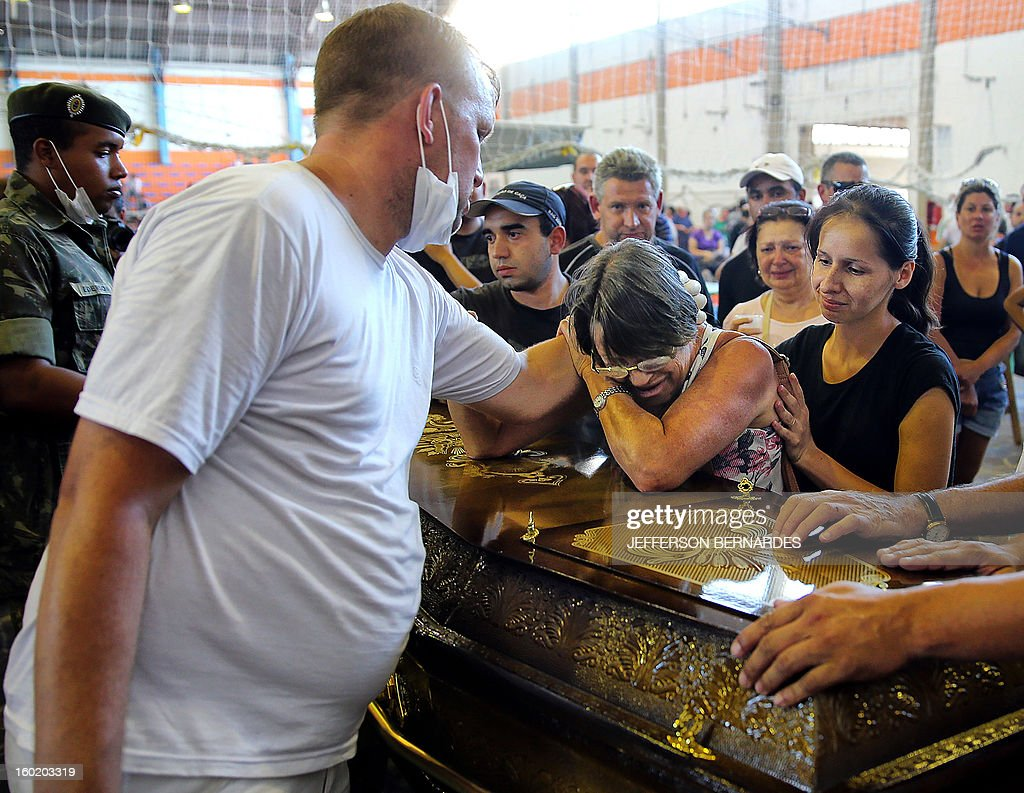 Relatives of victims from a fire that broke out at a nightclub weep, during their funeral in Santa Maria, 550 Km from Porto Alegre, southern Brazil on January 27, 2013. At least 232 people died and 131 were injured early Sunday when a fire tore through a nightclub packed with university students in the southern Brazilian city of Santa Maria, police said. AFP PHOTO / Jefferson BERNARDES